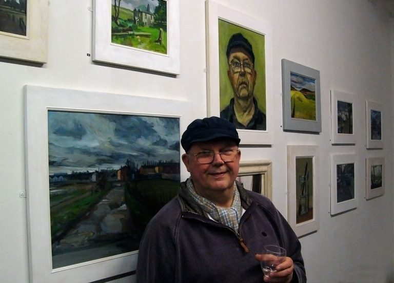 Photo of John Pegg at Stockport Art Gallery, 2015, standing in front of hung paintings.